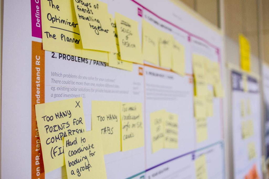 """Photo of sticky notes on a poster. The poster says """"Problems / Pain Points"""" and sticky notes say, for example, """"Hard to coordinate booking for a group"""""""